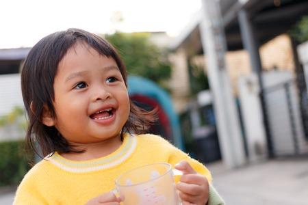 enjoys: Little girl enjoys drinking Stock Photo