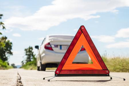 Emergency stop sign and broken car on road. Reklamní fotografie