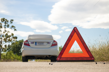 Emergency stop sign and broken car on road. Stock Photo
