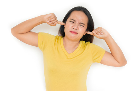 Woman closed her ears because of the annoying noise. isolated on white.