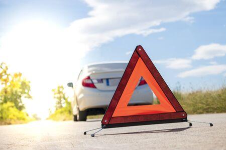 Emergency stop sign near broken car on road.