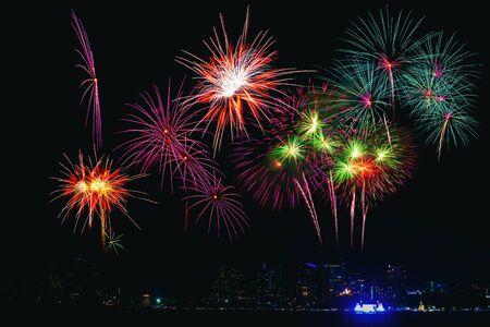 Piękne kolorowe fajerwerki na plaży nad morzem, niesamowita impreza z fajerwerkami świątecznymi lub każda uroczystość na ciemnym niebie. Zdjęcie Seryjne