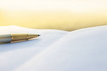 Low angle view of golden pen lying on white sheet of paper in a folder with another set of paperwork