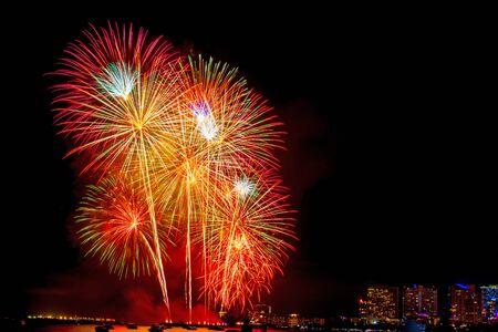Hermoso colorido espectáculo de fuegos artificiales en la playa del mar, increíble fiesta de fuegos artificiales navideños o cualquier evento de celebración en el cielo oscuro.
