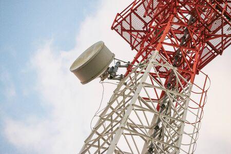 Wireless Communication Antenna Transmitter. Telecommunication tower with antennas on blue sky background.
