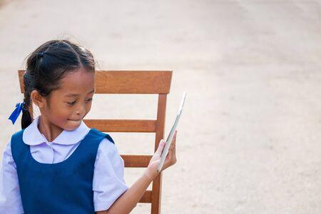 Happy little girl holding tablet PC outdoors in summer park 版權商用圖片