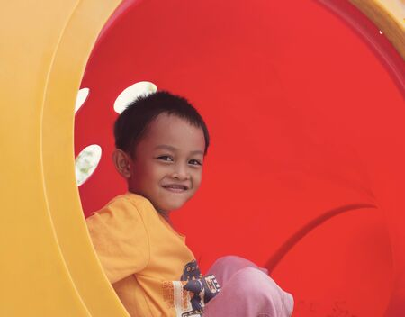 Happy smiles of boys on a colorful playground during the daytime.