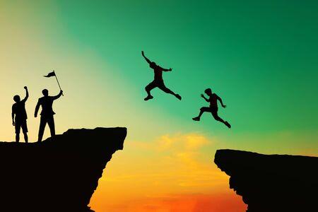 La gente saltó de los viejos obstáculos a nuevos logros. Concepto de trabajo en equipo. Foto de archivo