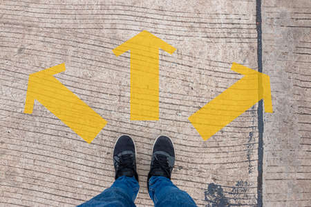 Person wearing sneakers standing on a concrete road with yellow arrows, Decision-making concept
