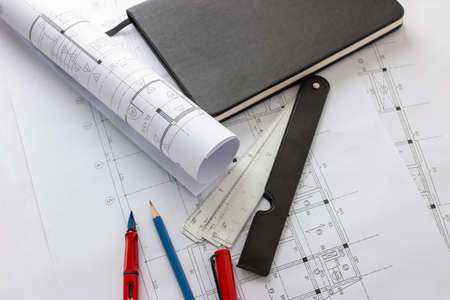Rolls of architecture blueprints and house plans on the table and architect drawing tools. Stock fotó