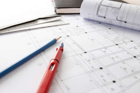 Rolls of architecture blueprints and house plans on the table and architect drawing tools. Imagens