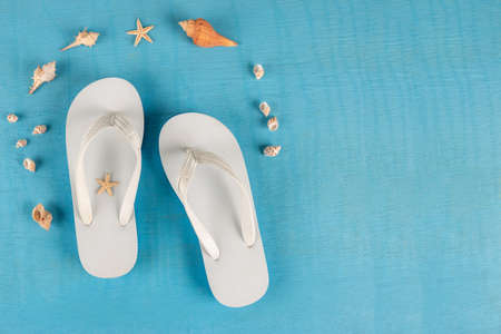 Summer beach sea accessories. flip flops, shells, starfish on blue background top view flat lay copy space. Summer background Holiday vacation travel concept