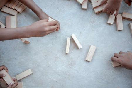 Children playing with wooden blocks on the concrete floor 版權商用圖片