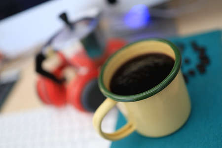 The work desk has a coffee cup and red headphones and office supplies.