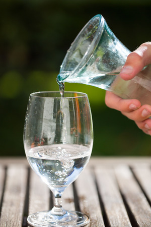 privatization: pouring a glass of water from bottle
