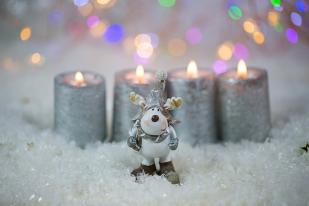 Candles with moose in snow, glittering background