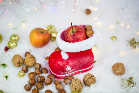 Santa Claus boots with nuts, tangerines, apples, in the snow