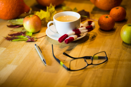 Coffee cup with glasses, in the background pumpkin, apples, leaves