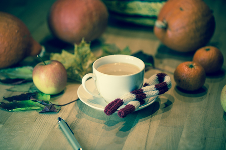 Coffee cup with pails, in the background pumpkin, leaves, apples