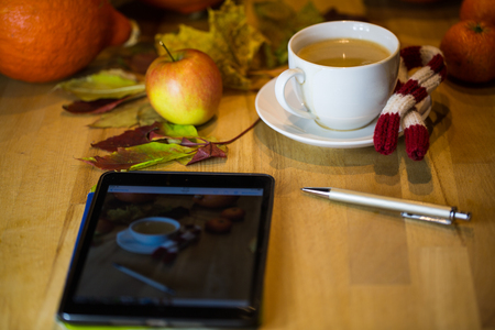 Coffee cup with tablet on the table, in the background pumpkin, leaves, apples Фото со стока