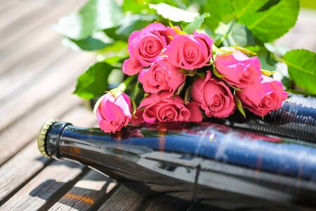 Beer bottle lying with roses for Fathers Day