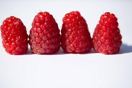 Raspberries strung, white background