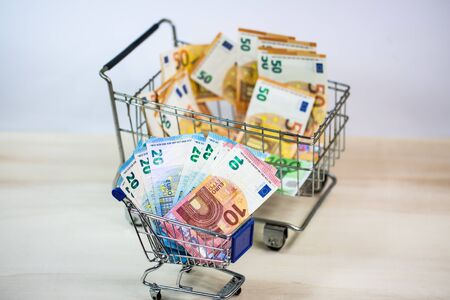 small and big shopping cart full of money, symbolic 版權商用圖片