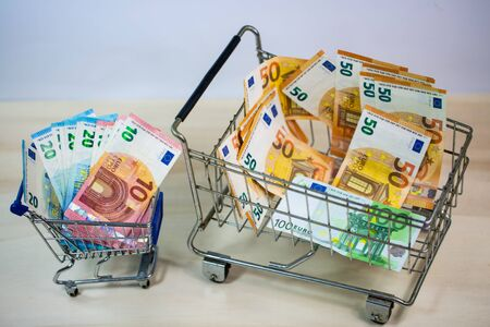 small and big shopping cart full of money, symbolic 版權商用圖片 - 131099915