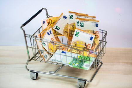 small and big shopping cart full of money, symbolic 版權商用圖片 - 131099917
