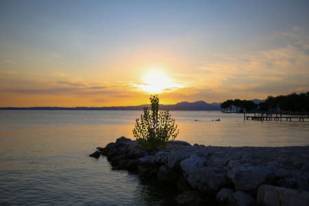 Sunset in Bardolino on Lake Garda with mountains in the background