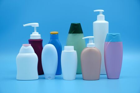 Set of various shampoo, conditioner, lotion plastic bottles on a blue background. Zdjęcie Seryjne