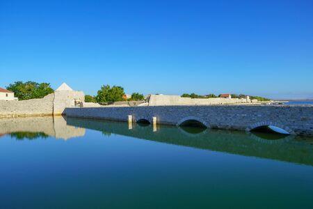 Bridge and old defensive walls of medieval town Nin in Dalmatia, Croatia Archivio Fotografico - 150294057