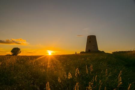 日没、ホイスト行く太陽を見てベンチに座ってカップル待っていた時計 Cleadom 丘に上がった