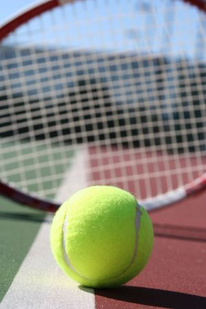 raquet: Tennis ball on a court line with a racquet in the background