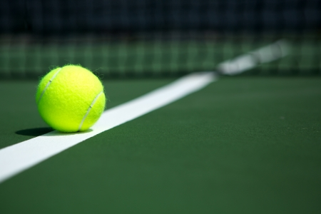 ball: Tennis Ball on the Court with the Net in the background Stock Photo