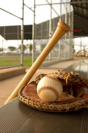 baseball dugout: Bate de b�isbol y guantes en el banco de la caseta