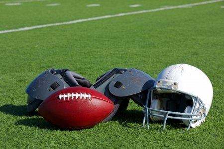 American Football and Helmet on the Field with Shoulder Pads photo