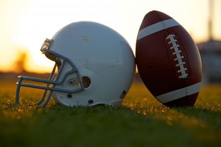 American Football and Helmet on the Field Backlit at Sunset