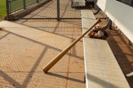 guante de beisbol: Bate de béisbol y guante en el banquillo del dugout