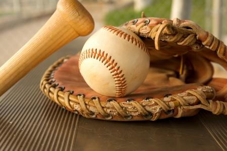 baseball dugout: Bate de b�isbol y guante en el banquillo del dugout