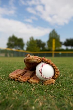 campo de beisbol: Béisbol nuevo en un guante en el jardín