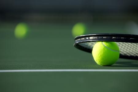 raqueta de tenis: Pelota de tenis y raqueta con más bolas en la distancia