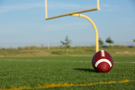 uprights: American Football and the goal posts in the distance