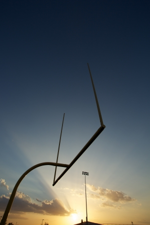 field sunset: American Football Goal Posts or Uprights at Sunset Stock Photo