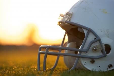 American Football Helm op het veld bij zonsondergang met ruimte voor kopiëren