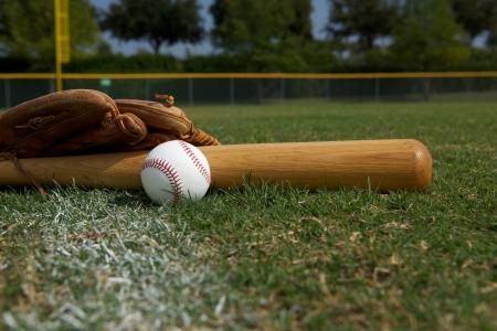 guante de beisbol: Bate de b�isbol y guante en la hierba con el espacio para la copia Foto de archivo