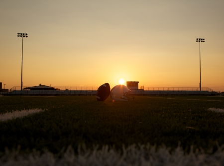 youth football: American Football and Helmet on the Field at Sunset with Stands Beyond
