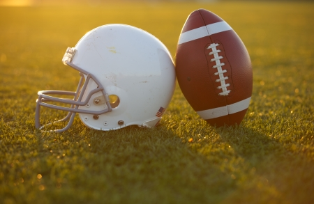 American Football and Helmet on the Field at Sunset Stock Photo