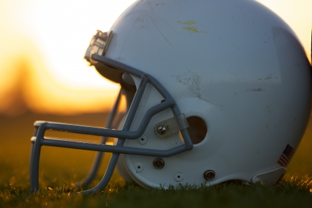 american football field: American Football Helmet on the Field at Sunset Stock Photo