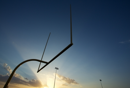 youth football: American Football Field Goal Posts or Uprights backlit by a setting sun with room for copy Stock Photo